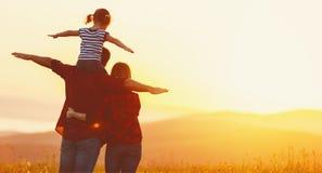 Familia feliz: padre de la madre e hija del niño en puesta del sol Foto de archivo