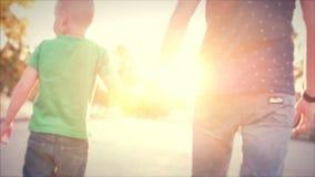 Familia feliz, padre feliz e hijo caminando con el hijo que lleva a cabo las manos Cantidad común metrajes