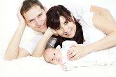 Familia feliz: padres con el bebé recién nacido de mentira fotografía de archivo