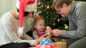 Familia feliz, padres que muestran las decoraciones de Ney Year a su niño lindo delante del árbol de navidad Madre en el sombrero foto de archivo libre de regalías