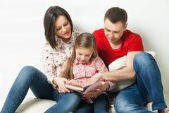 Familia feliz Parents el libro de lectura con la hija Fotografía de archivo