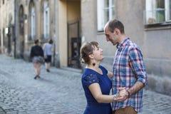 Familia feliz Pares en el baile del amor en el pavimento de la ciudad vieja Imagenes de archivo