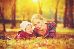 Familia feliz: pequeña hija de la madre y del niño que juega y que ríe en otoño Imagen de archivo