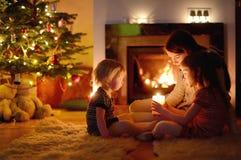 Familia feliz por una chimenea en la Navidad foto de archivo libre de regalías