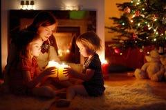 Familia feliz por una chimenea en la Navidad Imagenes de archivo