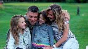 Familia feliz que abraza en la hierba almacen de metraje de vídeo