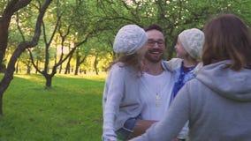 Familia feliz que abraza en la hierba Los padres y sus dos hijas están abrazando en el césped del parque Huerta floreciente almacen de metraje de vídeo