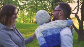 Familia feliz que abraza en la hierba Los padres y sus dos hijas están abrazando en el césped del parque Huerta floreciente almacen de video