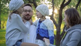 Familia feliz que abraza en un parque floreciente almacen de metraje de vídeo
