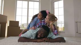 Familia feliz que abraza mientras que hace la pila en la alfombra metrajes
