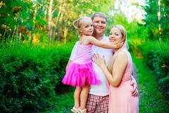 Familia feliz que abraza y que camina al aire libre imagenes de archivo