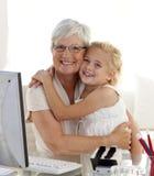 Familia feliz que abraza y que computa imágenes de archivo libres de regalías