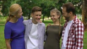 Familia feliz que abraza y que sonríe en el parque, presentando en cámara, orgullo para los niños almacen de video