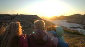Familia feliz que admira la puesta del sol o la salida del sol en la orilla del norte rocosa del mar almacen de metraje de vídeo
