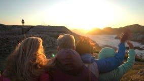 Familia feliz que admira la puesta del sol o la salida del sol en la orilla del norte rocosa del mar almacen de video