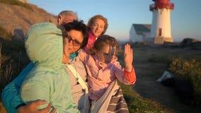 Familia feliz que admira la puesta del sol o la salida del sol en la orilla del norte rocosa del mar con un faro viejo metrajes