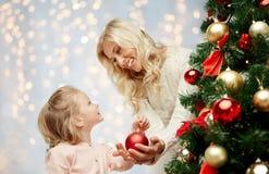 Familia feliz que adorna el árbol de navidad Imagen de archivo