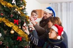 Familia feliz que adorna el árbol de navidad Foto de archivo