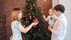 Familia feliz que adorna el árbol de navidad almacen de metraje de vídeo