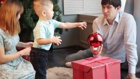 Familia feliz que adorna el árbol de navidad almacen de video