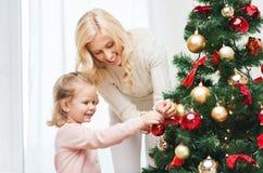 Familia feliz que adorna el árbol de navidad en casa Foto de archivo libre de regalías