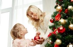 Familia feliz que adorna el árbol de navidad en casa Imagenes de archivo
