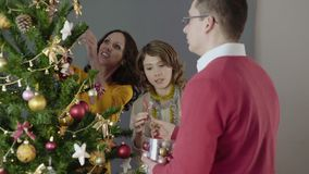 Familia feliz que adorna el árbol de navidad, preparándose para el día de fiesta, humor festivo metrajes