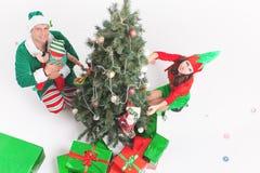 Familia feliz que adorna el árbol de navidad, vestido en trajes del duende Fotos de archivo libres de regalías