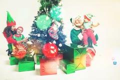 Familia feliz que adorna el árbol de navidad, vestido en trajes del duende Imágenes de archivo libres de regalías
