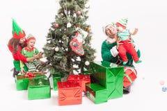 Familia feliz que adorna el árbol de navidad, vestido en trajes del duende Fotos de archivo