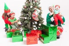 Familia feliz que adorna el árbol de navidad, vestido en trajes del duende Fotografía de archivo libre de regalías