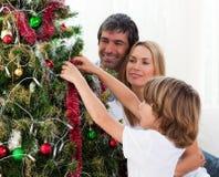 Familia feliz que adorna un árbol de navidad Imágenes de archivo libres de regalías