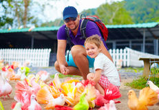 Familia feliz que alimenta pájaros coloridos de la paloma en granja Imagen de archivo libre de regalías