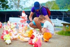 Familia feliz que alimenta pájaros coloridos de la paloma en granja Imagenes de archivo
