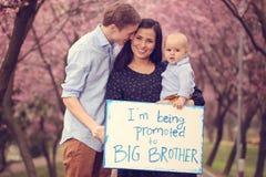 Familia feliz que anuncia nueva llegada del bebé Imágenes de archivo libres de regalías
