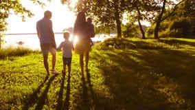 Familia feliz que camina cerca del mar Campo y árboles en campo Colores calientes de la puesta del sol o de la salida del sol Pad metrajes