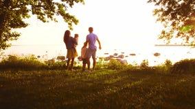 Familia feliz que camina cerca del mar Campo y árboles en campo Colores calientes de la puesta del sol o de la salida del sol Pad almacen de metraje de vídeo