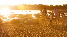 Familia feliz que camina cerca del mar Playa y oc?ano Colores calientes de la puesta del sol o de la salida del sol Padres de amo almacen de metraje de vídeo