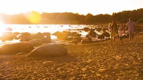 Familia feliz que camina cerca del mar Playa y oc?ano Colores calientes de la puesta del sol o de la salida del sol Padres de amo almacen de video