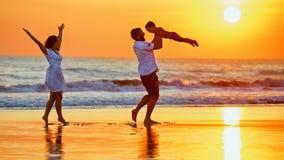 Familia feliz que camina con la diversión en la playa del mar de la puesta del sol foto de archivo