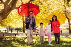 Familia feliz que camina con los paraguas en el parque Foto de archivo