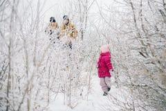 Familia feliz que camina en el bosque nevoso Imagenes de archivo