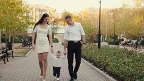 Familia feliz que camina en el parque almacen de metraje de vídeo