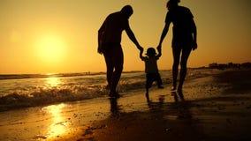 Familia feliz que camina en la familia feliz de la costa de mar con un niño el vacaciones en la playa Puesta del sol de las silue almacen de metraje de vídeo