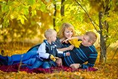Familia feliz que camina en la naturaleza del otoño Foto de archivo libre de regalías