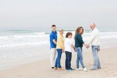 Familia feliz que camina en la playa foto de archivo