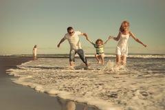 Familia feliz que camina en la playa en el tiempo del día Imagen de archivo
