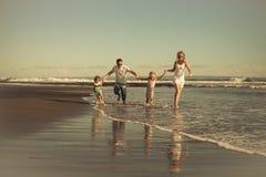 Familia feliz que camina en la playa en el tiempo del día Fotos de archivo
