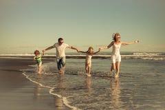 Familia feliz que camina en la playa en el tiempo del día Imagen de archivo libre de regalías