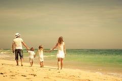 Familia feliz que camina en la playa en el tiempo del día imagenes de archivo
